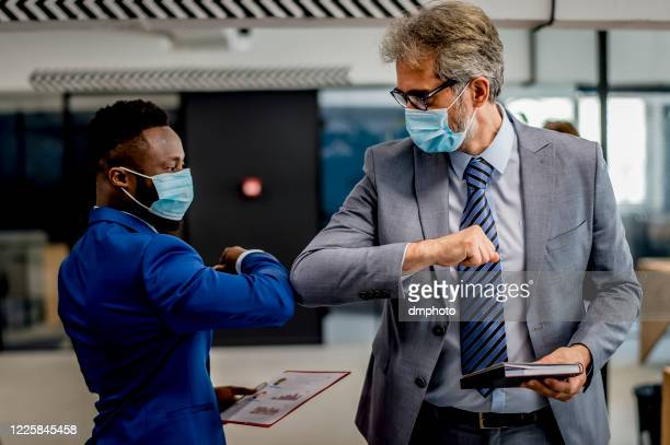 business people greeting during covid-19 pandemic, elbow bump - elbow bump stock pictures, royalty-free photos & images