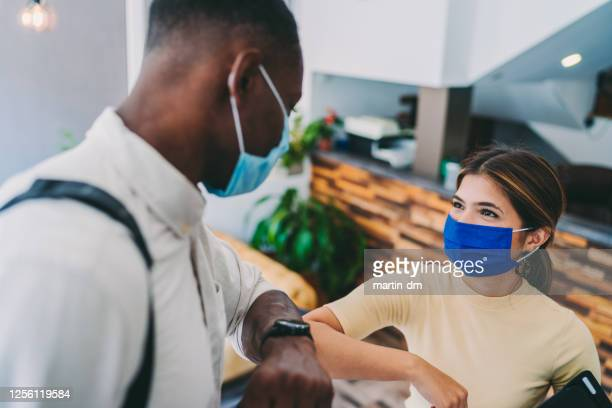 business people greeting during covid-19 pandemic, elbow bump - avoidance stock pictures, royalty-free photos & images