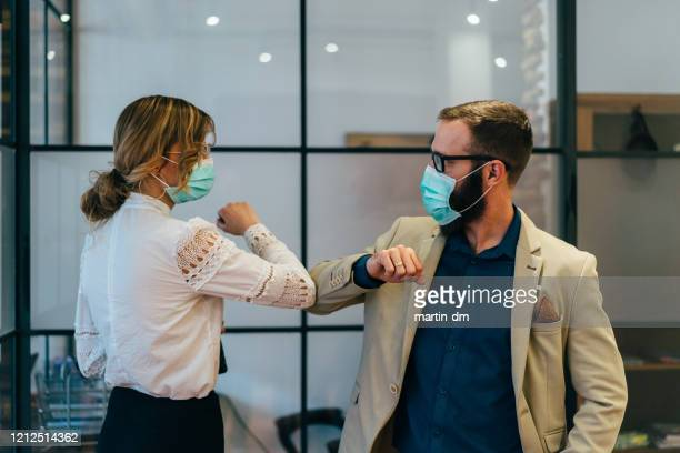 business people greeting during covid-19 pandemic - protective face mask stock pictures, royalty-free photos & images