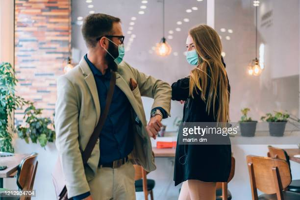 business people greeting during covid-19 pandemic - elbow bump stock pictures, royalty-free photos & images