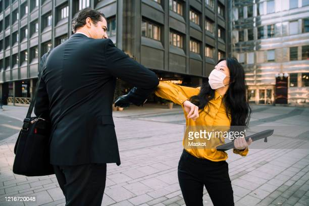business people greeting during virus pandemic - elbow bump stock pictures, royalty-free photos & images