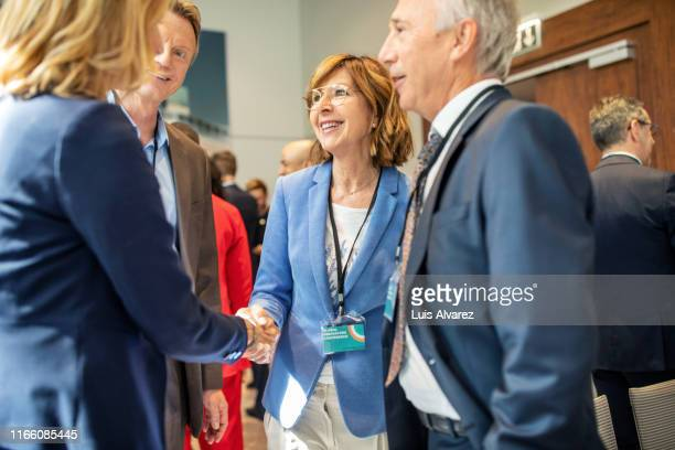 business people greeting each other in convention center - convention center stock pictures, royalty-free photos & images
