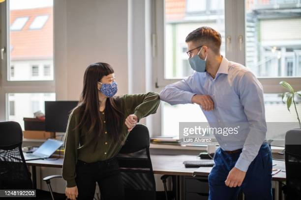 business people greeting with elbow bump in office - entrepreneur stock pictures, royalty-free photos & images