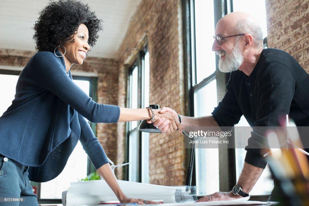 Business people handshaking over blueprints on desk : Stock Photo