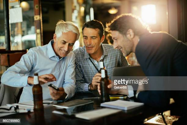 business people having a drink and using a phone - after work stock pictures, royalty-free photos & images