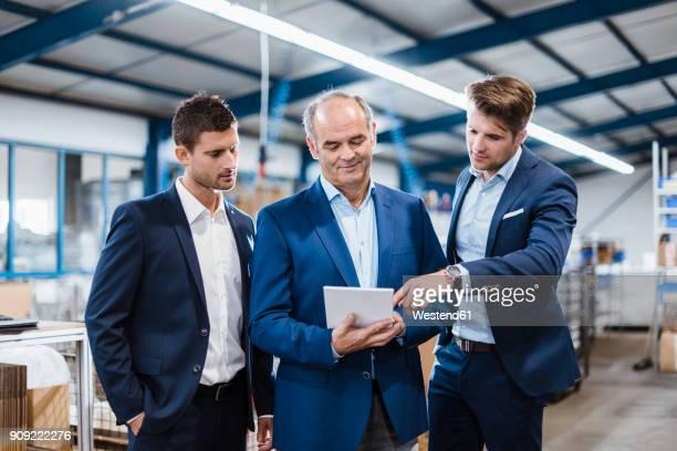 business people having a meeting in company shop floor - three people stock-fotos und bilder