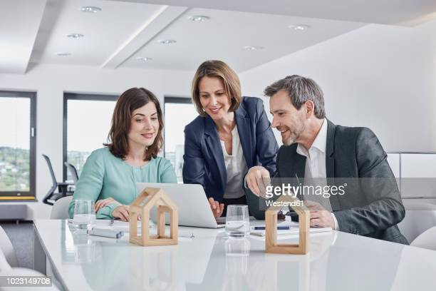 Business people having a meeting in office with laptop and architectural models