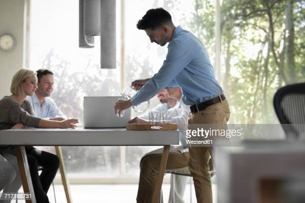 Business people having a meeting in office, young man pouring water into glasses