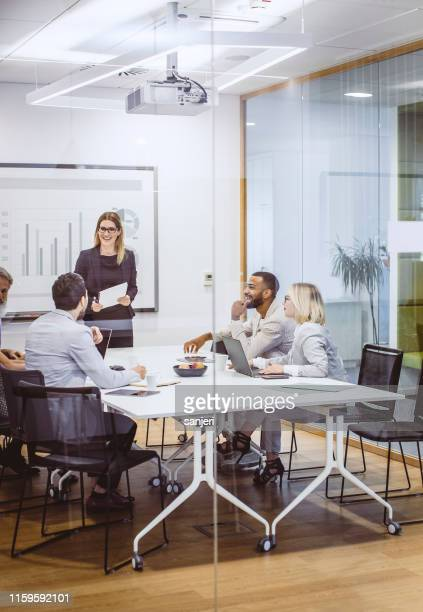 zakenmensen die een meeting hebben in de board room - verticaal stockfoto's en -beelden