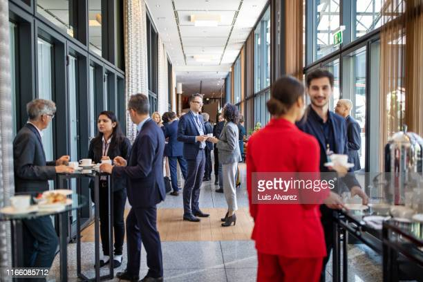 business people having a refreshment break at conference - sociale bijeenkomst stockfoto's en -beelden