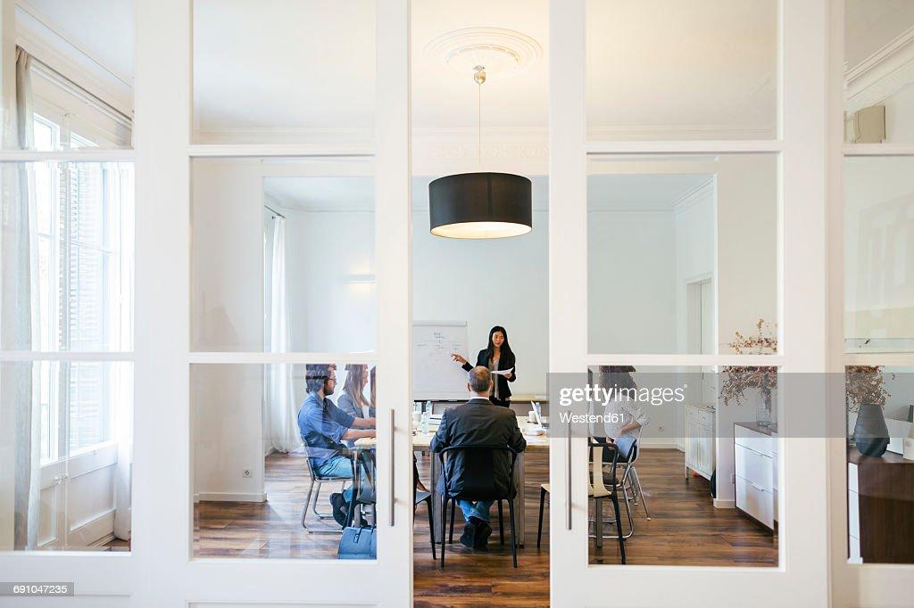 Business People Having A Team Meeting Behind Glass Doors Stock Photo