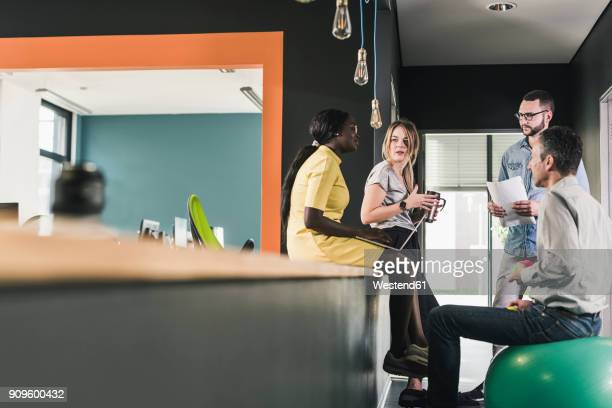 business people having an informal meeting in office - fitness ball stock pictures, royalty-free photos & images