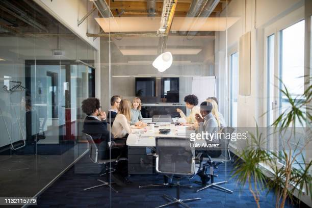 business people having board meeting in modern office - meeting photos et images de collection