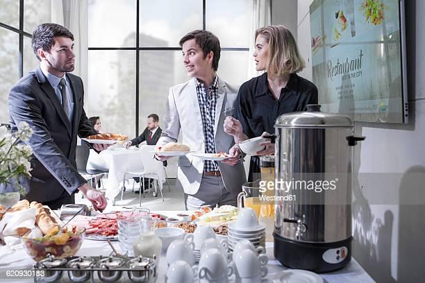 Business people having buffet breakfast at hotel