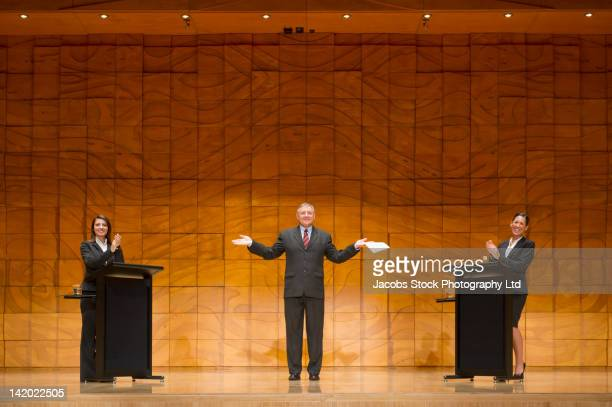 business people having debate on stage - debate stock photos and pictures
