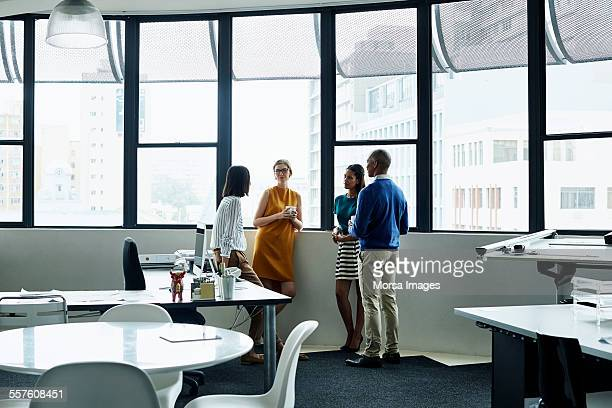 Business people having discussion by window