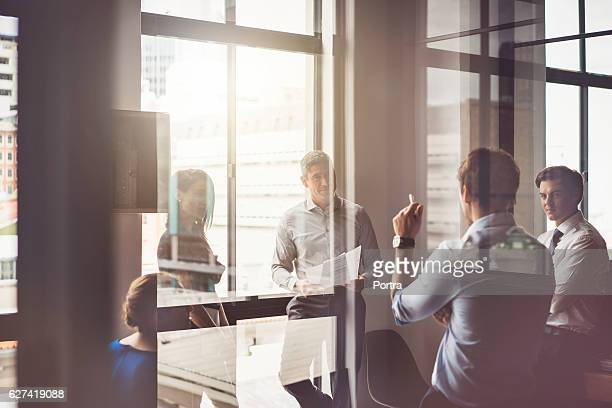business people having discussion in board room - zakenbijeenkomst stockfoto's en -beelden