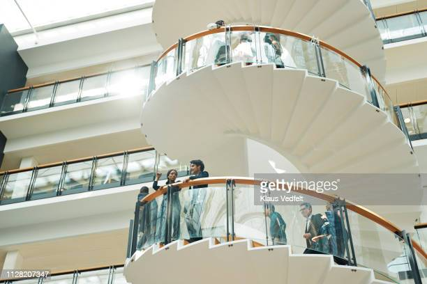 Business people having discussion on staircase in modern office building