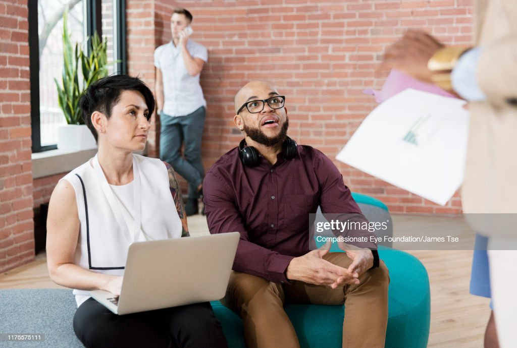 Business people having informal meeting in open plan office : Stock Photo