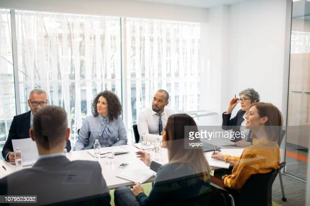 business people having meeting in a conference room - medium group of people stock pictures, royalty-free photos & images