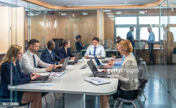 business people having meeting in conference room - older women in short skirts stock pictures, royalty-free photos & images