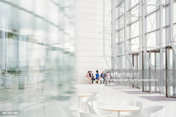 business people having meeting in modern lobby - distant stock pictures, royalty-free photos & images