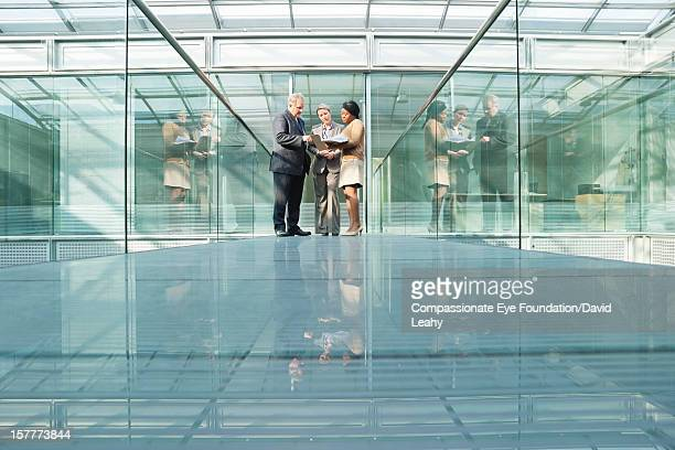 business people having meeting on atrium balcony - building atrium stock pictures, royalty-free photos & images