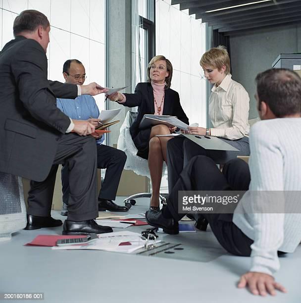 Business people having meeting, woman and man passing paperwork