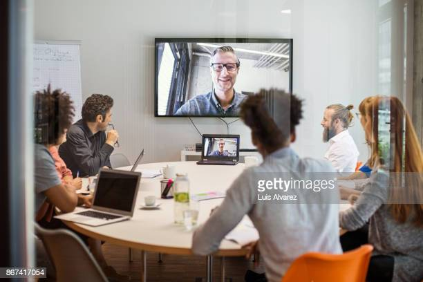 business people having video conference meeting in board room - virtual meeting stock pictures, royalty-free photos & images
