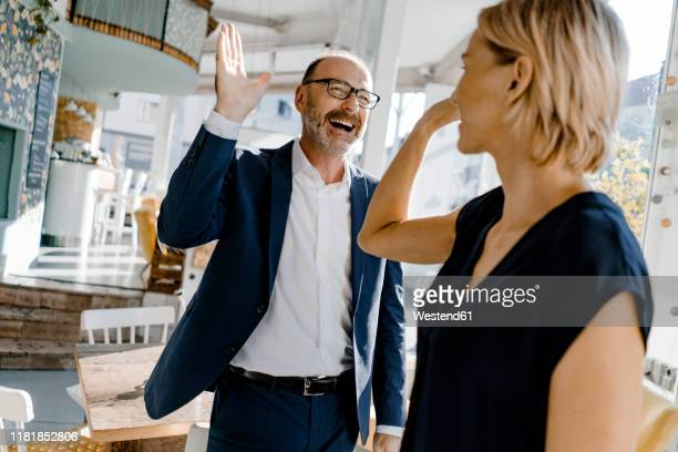 business people high fiving in a coffee shop - high five stock-fotos und bilder
