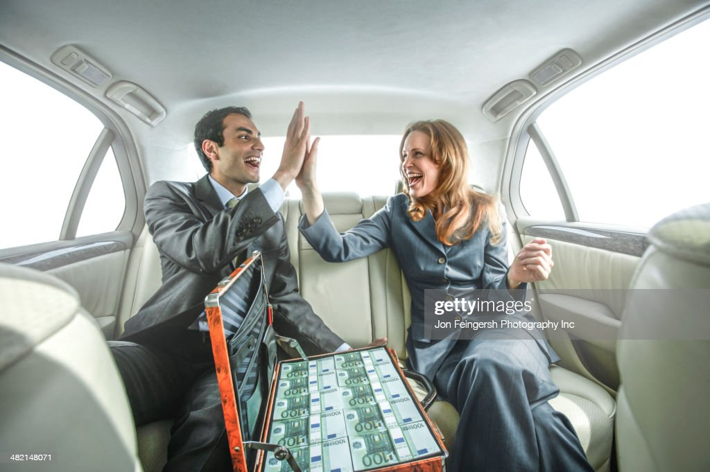 Business people high fiving in backseat of car : Stock Photo