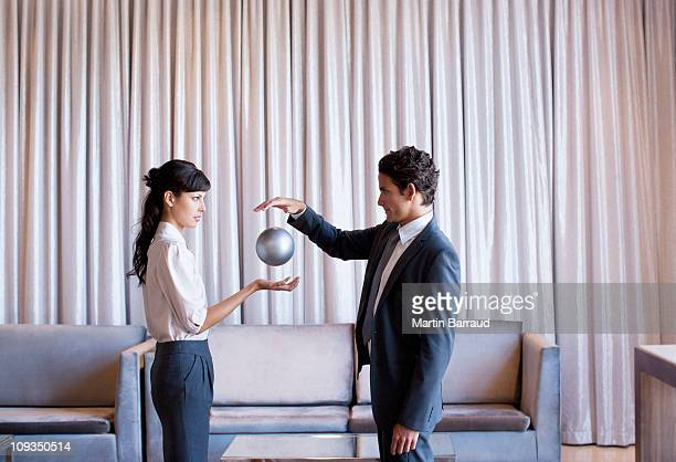 business people high-fiving in hotel lobby - goochelaar stockfoto's en -beelden