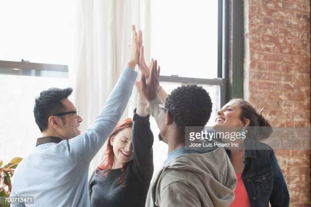 business people high-fiving in office - high five stock pictures, royalty-free photos & images