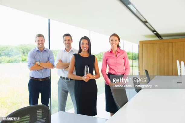 Business people holding award in modern office