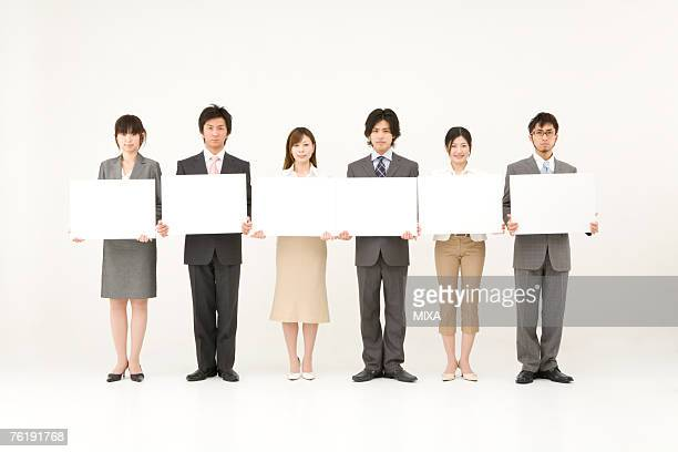 Business people holding blank placards