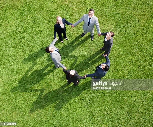 Geschäftsleute, die Hände im Kreis im Freien