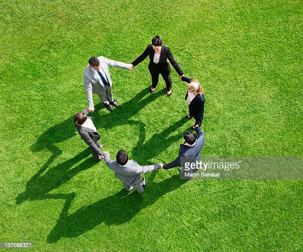 Business people holding hands in circle outdoors