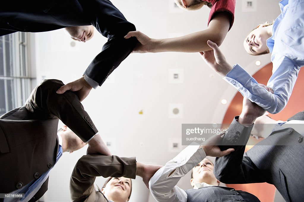 Business people holding hands in circle : Stock-Foto
