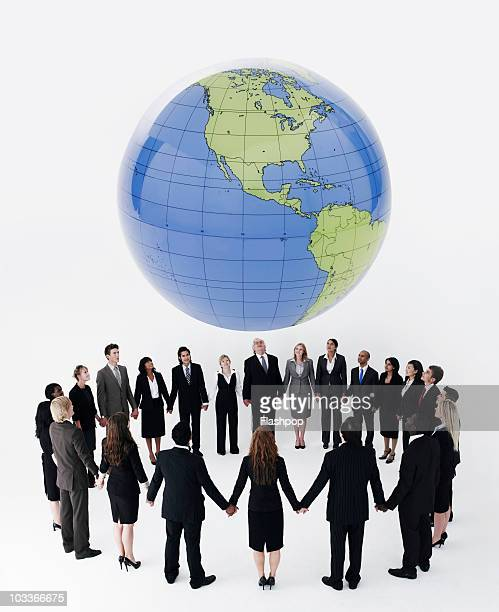 Business people holding hands under globe