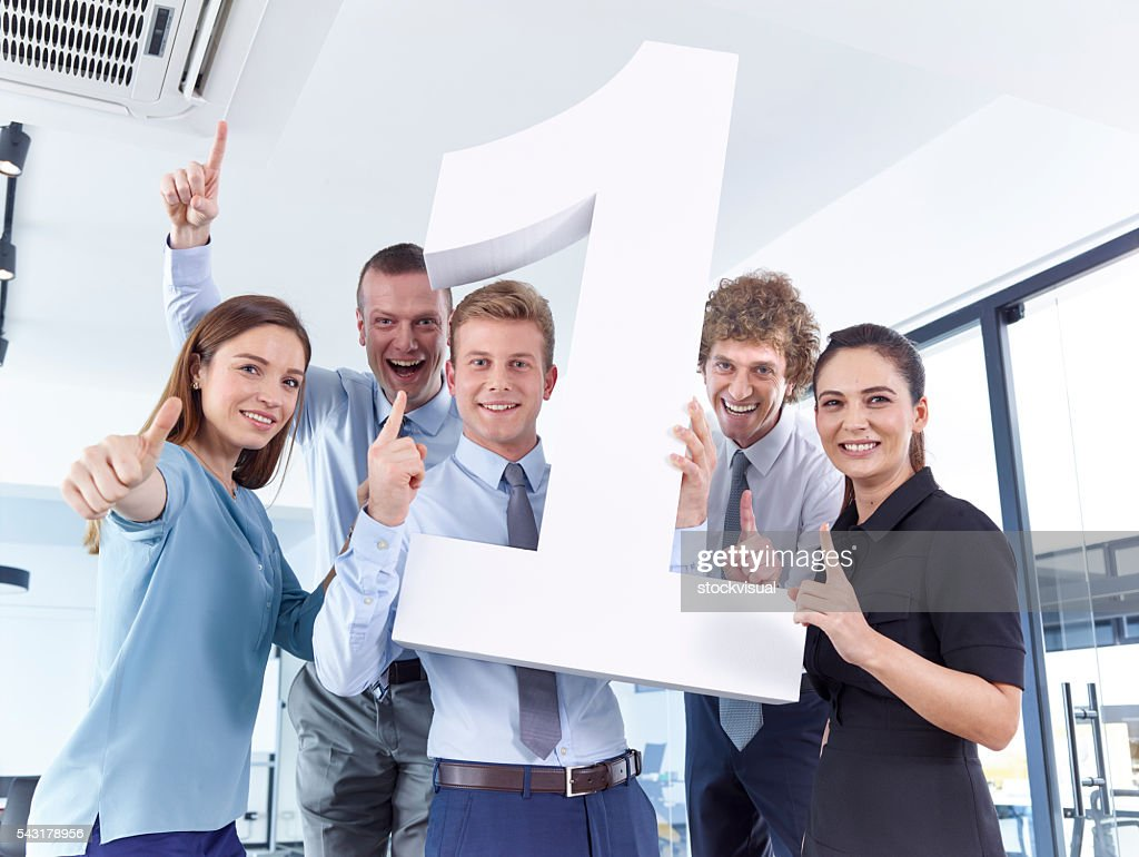 Business people holding large number 1 : Stock Photo