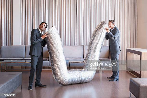 Business people holding metal tubing in hotel lobby