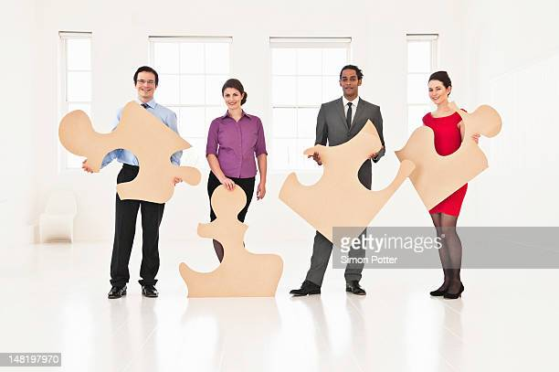 Business people holding puzzle pieces