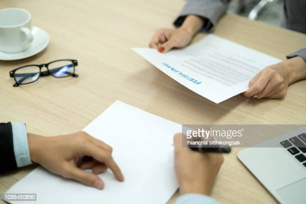 business people holding resume on table in office - unemployment stock photos and pictures