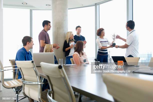 Business people holding trophy in office meeting