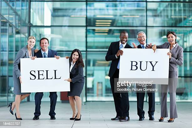 Business people holding up 'buy' and 'sell' boards