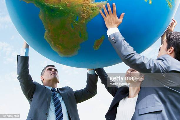 business people holding up large ball together - man with big balls stock photos and pictures