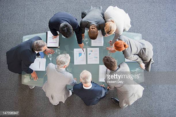 Business people huddled around paperwork on table