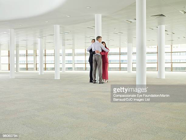 business people hugging around a pillar - compassionate eye foundation stock pictures, royalty-free photos & images