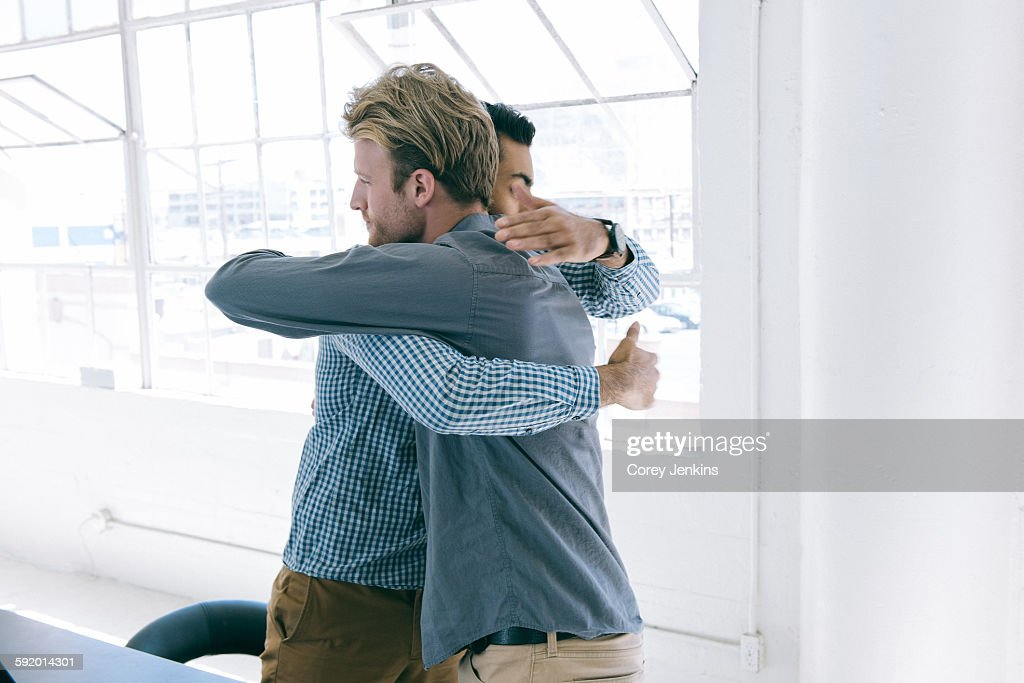 Business people hugging at meeting : Stock Photo