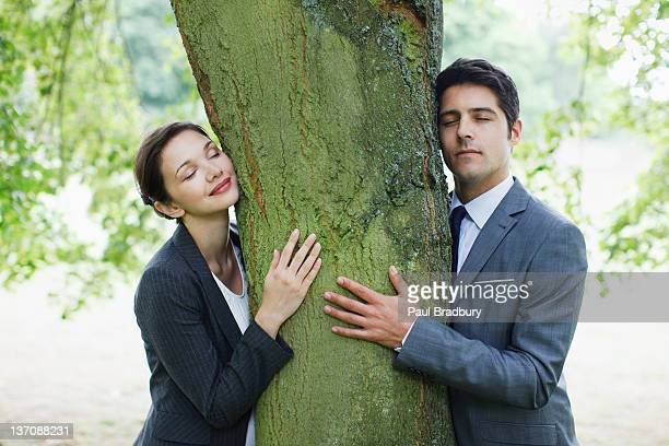 business people hugging tree - responsible business stock photos and pictures